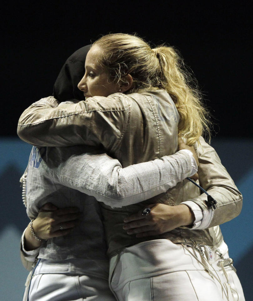 Mariel Zagunis, right, Ibtihaj Muhammad and Dagmara Wozniak, obscured, of the United States fencing team, celebrate after beating Mexico in the women's sabre team final at the Pan American Games in Guadalajara, Mexico, Friday, Oct. 28, 2011. (AP Photo/Jorge Saenz)