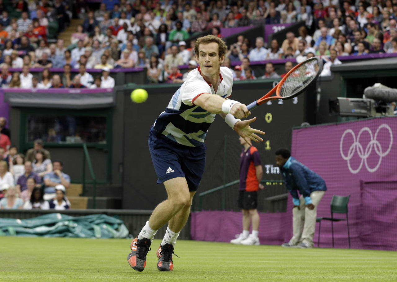 Andy Murray of Great Britain returns to Stanislas Wawrinka of Switzerland during their match at the All England Lawn Tennis Club in Wimbledon, London at the 2012 Summer Olympics, Sunday, July 29, 2012. (AP Photo/Elise Amendola)