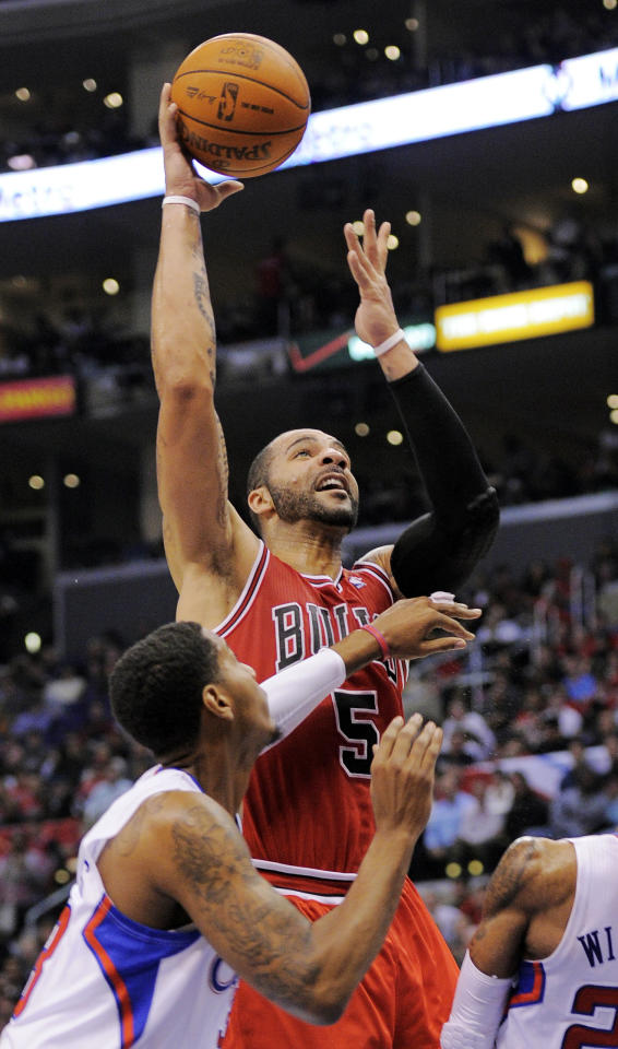 Chicago Bulls power forward Carlos Boozer (5) puts up a shot as Los Angeles Clippers forward Trey Thompkins defends during the first half of their NBA basketball game, Friday, Dec. 30, 2011, in Los Angeles. (AP Photo/Mark J. Terrill)