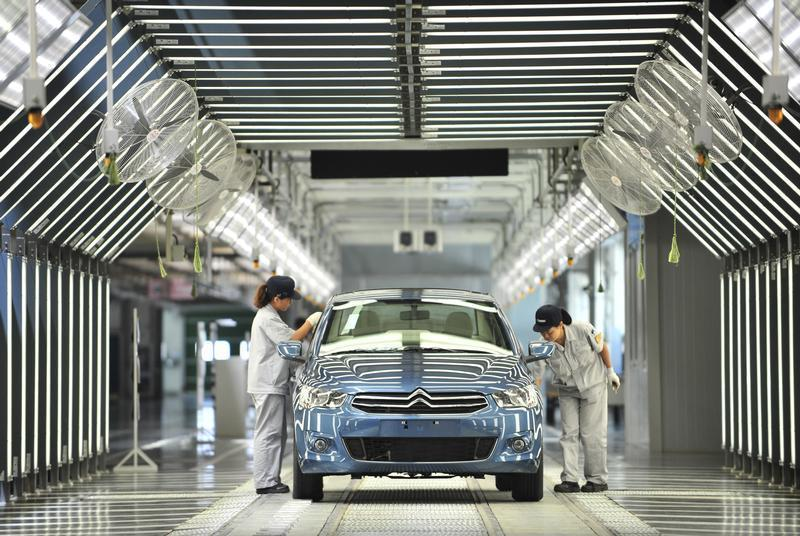 Employees work at the third factory of Dongfeng Peugeot Citroen Automobile company, after its inauguration ceremony, in Wuhan