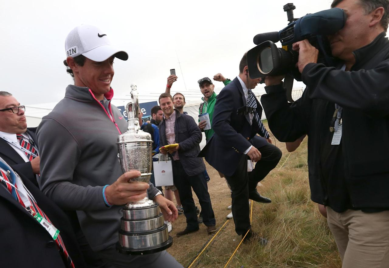 Rory McIlroy of Northern Ireland leaves the course holding the Claret Jug trophy after winning the British Open Golf championship at the Royal Liverpool golf club, Hoylake, England, Sunday July 20, 2014. (AP Photo/Scott Heppell)