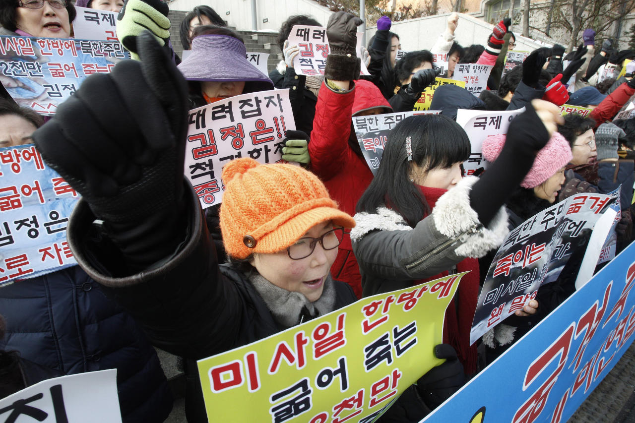 """South Korean house wives shout slogans during a rally denouncing North Korea's rocket launch in Seoul, South Korea, Thursday, Dec. 13, 2012. North Korea successfully fired a long-range rocket on Wednesday, defying international warnings as the regime of Kim Jong Un took a big step forward in its quest to develop a nuclear missile. The letters read """" Denounce North Korea's rocket launch and beat Kim Joung Un"""". (AP Photo/Ahn Young-joon)"""