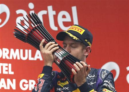 Red Bull Formula One driver Sebastian Vettel of Germany kisses his trophy on the podium after winning the Indian F1 Grand Prix at the Buddh International Circuit in Greater Noida, on the outskirts of New Delhi, October 27, 2013. REUTERS/Ahmad Masood