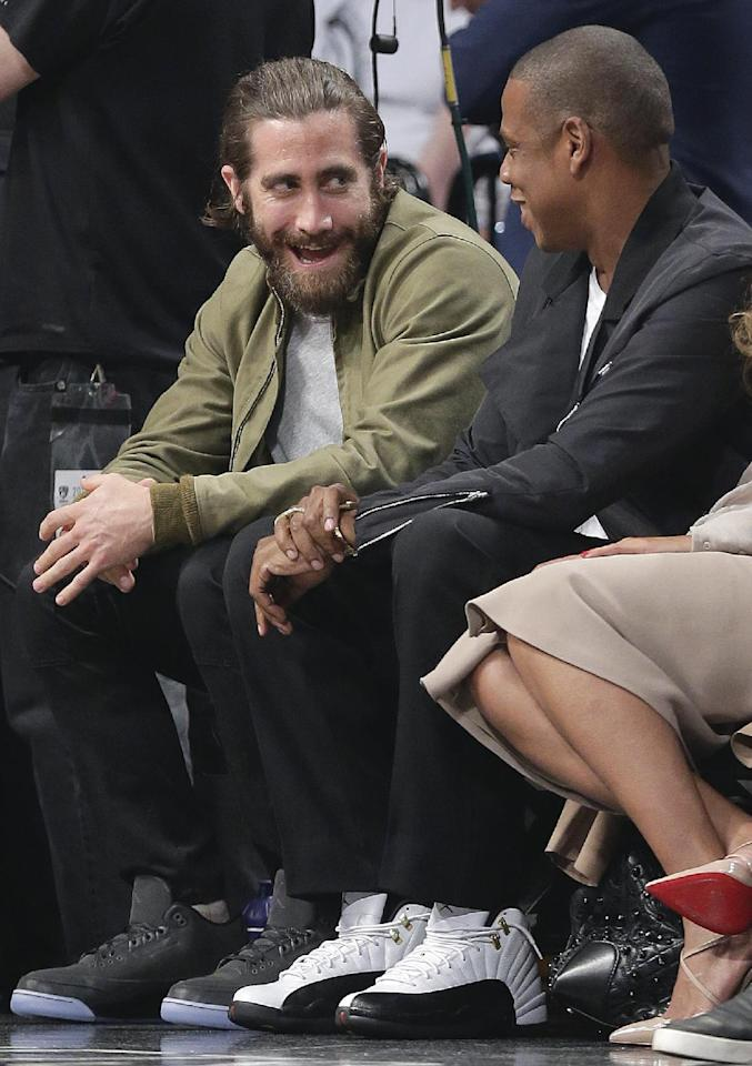 Actor Jake Gyllenhaal, left, and entertainer Jay-Z talk during a timeout during Game 3 of an Eastern Conference semifinal NBA playoff basketball game between the Miami Heat and the Brooklyn Nets, Saturday, May 10, 2014, in New York. (AP Photo/Julie Jacobson)