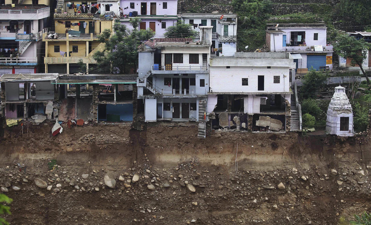 A view of damaged houses is seen following monsoon rains in Trivada, India, Wednesday, June 26, 2013. Paramilitary soldiers on Wednesday recovered 20 bodies from a steep hillside in northern India where a helicopter crashed while on a mission to rescue people stranded in monsoon floods, the country's air force chief said. The helicopter crashed late Tuesday when its rotor blades hit the hillside while returning with survivors of flooding and landslides that have killed more than 1,000 people and washed away thousands of homes, roads and bridges since mid-June in the Himalayan state of Uttarakhand. (AP Photo/Rafiq Maqbool)