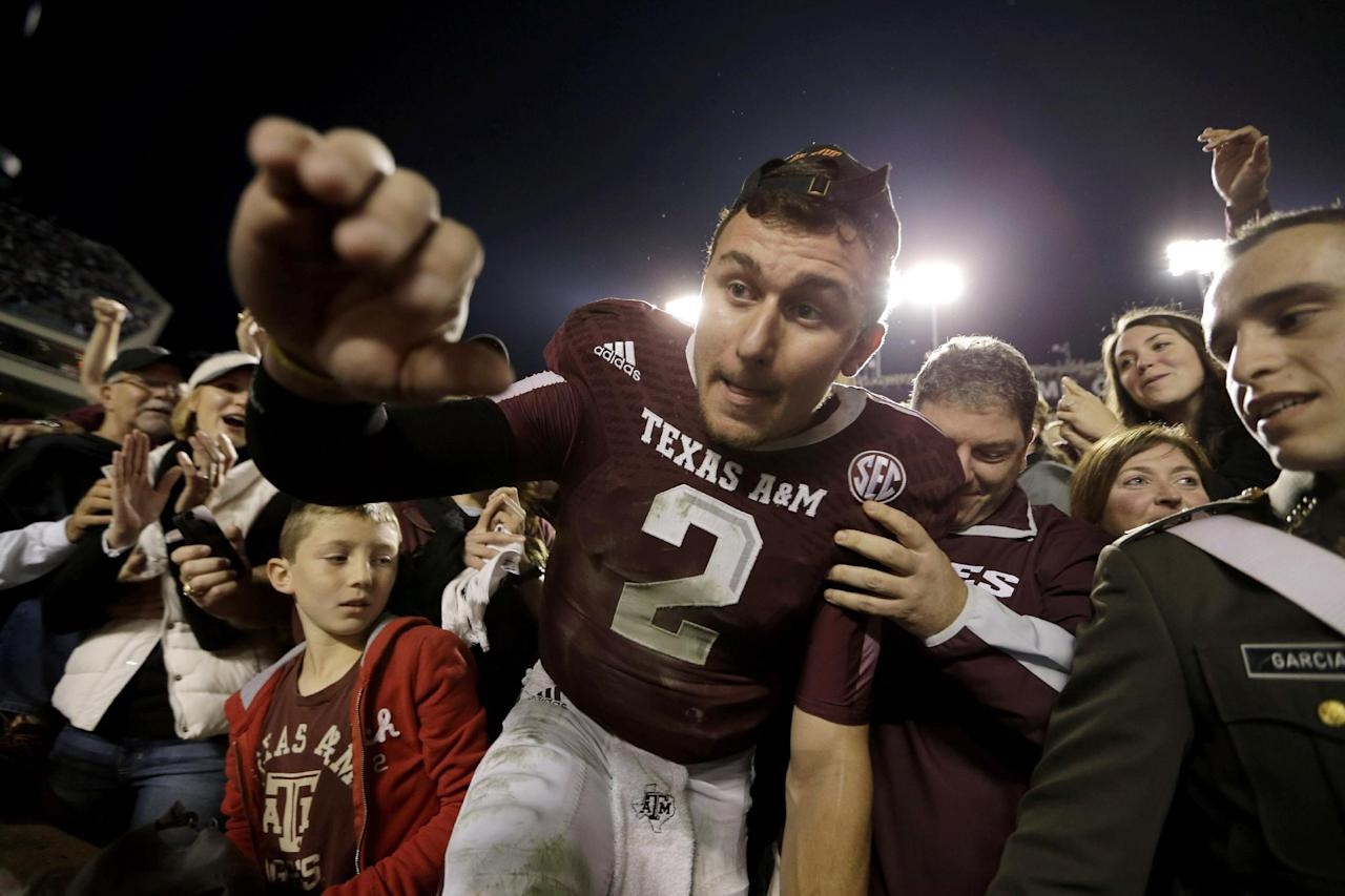Texas A&M quarterback Johnny Manziel (2) crawls out of the crowd after celebrating with fans after an NCAA college football game against Mississippi State Saturday, Nov. 9, 2013, in College Station, Texas. Texas A&M won 51-41. (AP Photo/David J. Phillip)