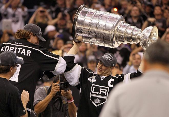 LOS ANGELES, CA - JUNE 14:  Anze Kopitar #11 of the Los Angeles Kings gives team captain Dustin Brown #23 a playful elbow bump as Brown carries the Stanley Cup to center ice during the rally in Staples Center after the Los Angeles Kings Stanley Cup Victory Parade on June 14, 2012 in Los Angeles, California.  (Photo by Victor Decolongon/Getty Images)