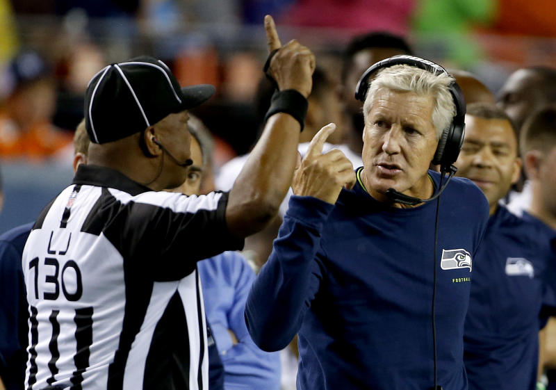 Seattle Seahawks coach Pete Carroll talks to line judge Darryll Lewis (130) during the second half of an NFL preseason football game against the Denver Broncos, Thursday, Aug. 7, 2014, in Denver