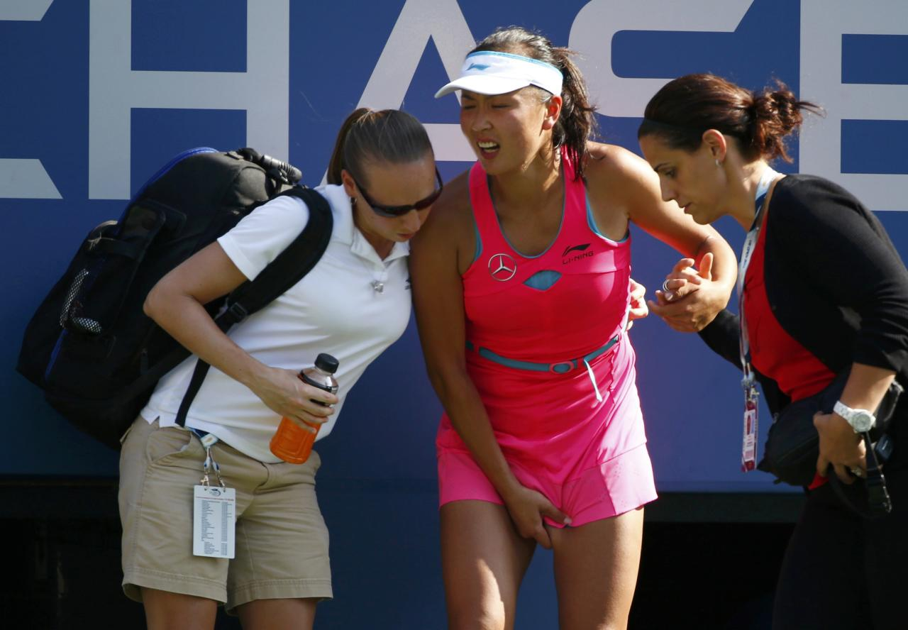 Peng Shuai of China is tended to as she begins to cramp up during the semi-final match against Caroline Wozniacki of Denmark at the 2014 U.S. Open tennis tournament in New York, September 5, 2014. REUTERS/Adam Hunger (UNITED STATES - Tags: SPORT TENNIS TPX IMAGES OF THE DAY)