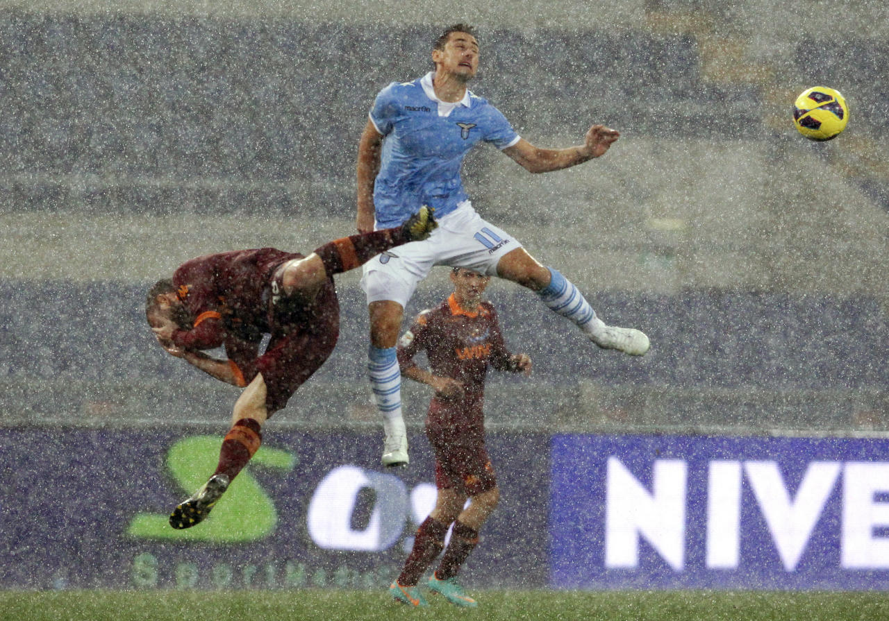 AS Roma's Daniele De Rossi (L) jumps for the ball with SS Lazio's Miroslav Klose during their Italian Serie A soccer match at the Olympic stadium in Rome November 11, 2012. Lazio won 3-2.