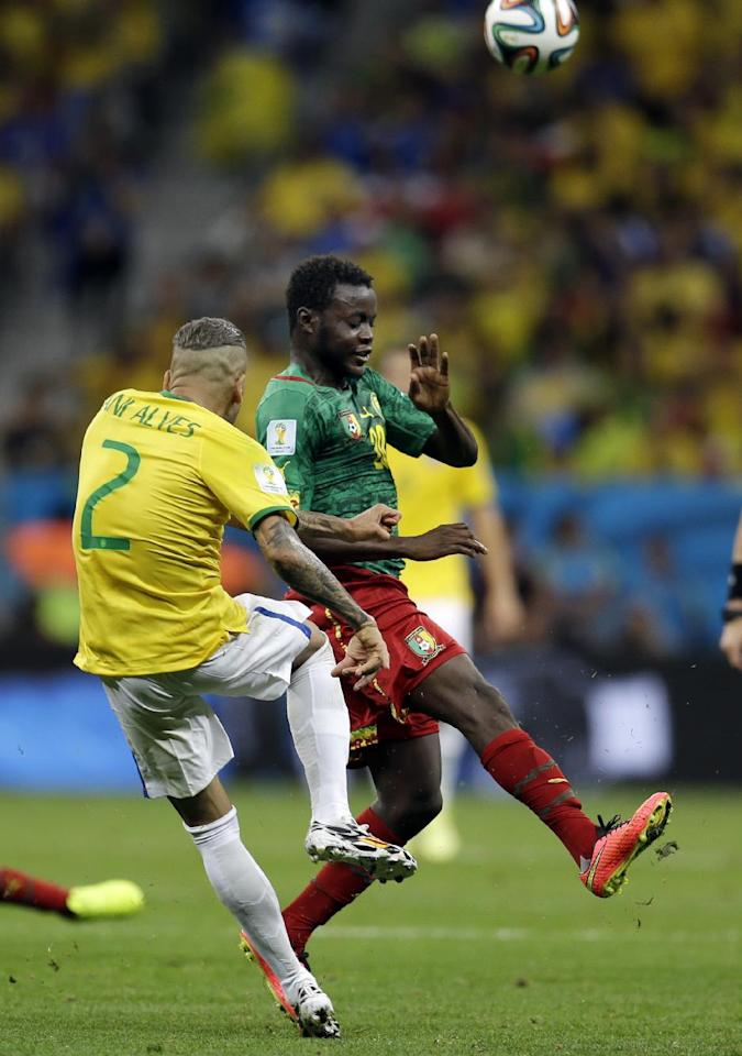 Cameroon's Edgar Salli runs in to block a kick by Brazil's Dani Alves during the group A World Cup soccer match between Cameroon and Brazil at the Estadio Nacional in Brasilia, Brazil, Monday, June 23, 2014. (AP Photo/Natacha Pisarenko)
