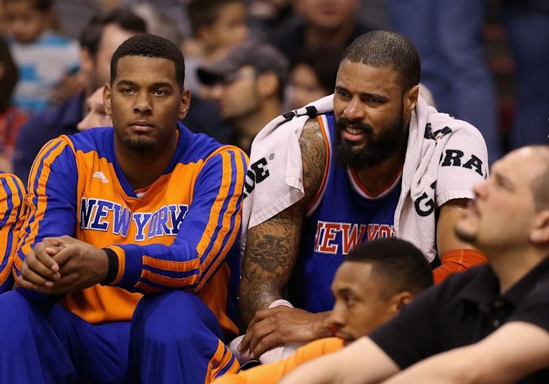 Tyson Chandler (R) of the New York Knicks holds ice on his right arm as he sits on the bench during the first half of a game against the Phoenix Suns at US Airways Center on March 28, 2014 in Phoenix, Arizona