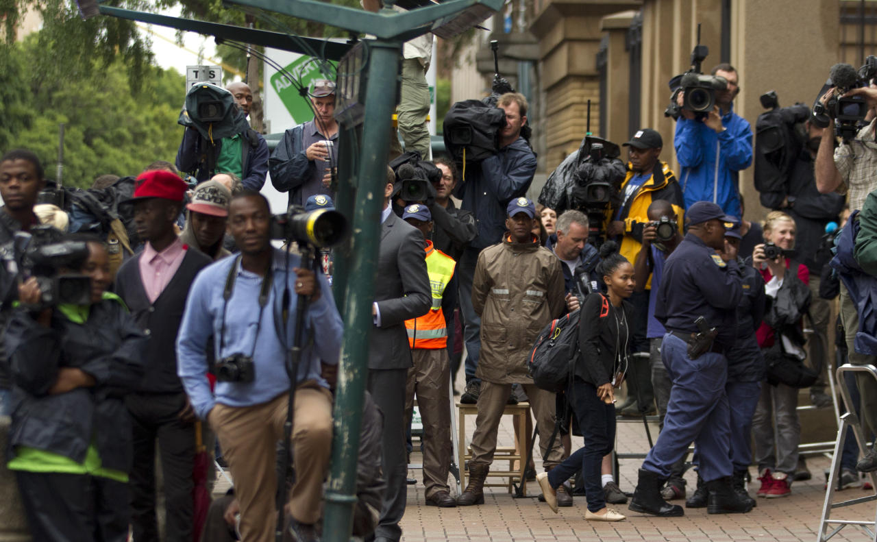 Members of the media and police officers await the arrival of Oscar Pistorius at the high court for his murder trial in Pretoria, South Africa, Tuesday, March 11, 2014. Pistorius is charged with murder for the shooting death of his girlfriend, Reeva Steenkamp, on Valentines Day in 2013. (AP Photo/Themba Hadebe)