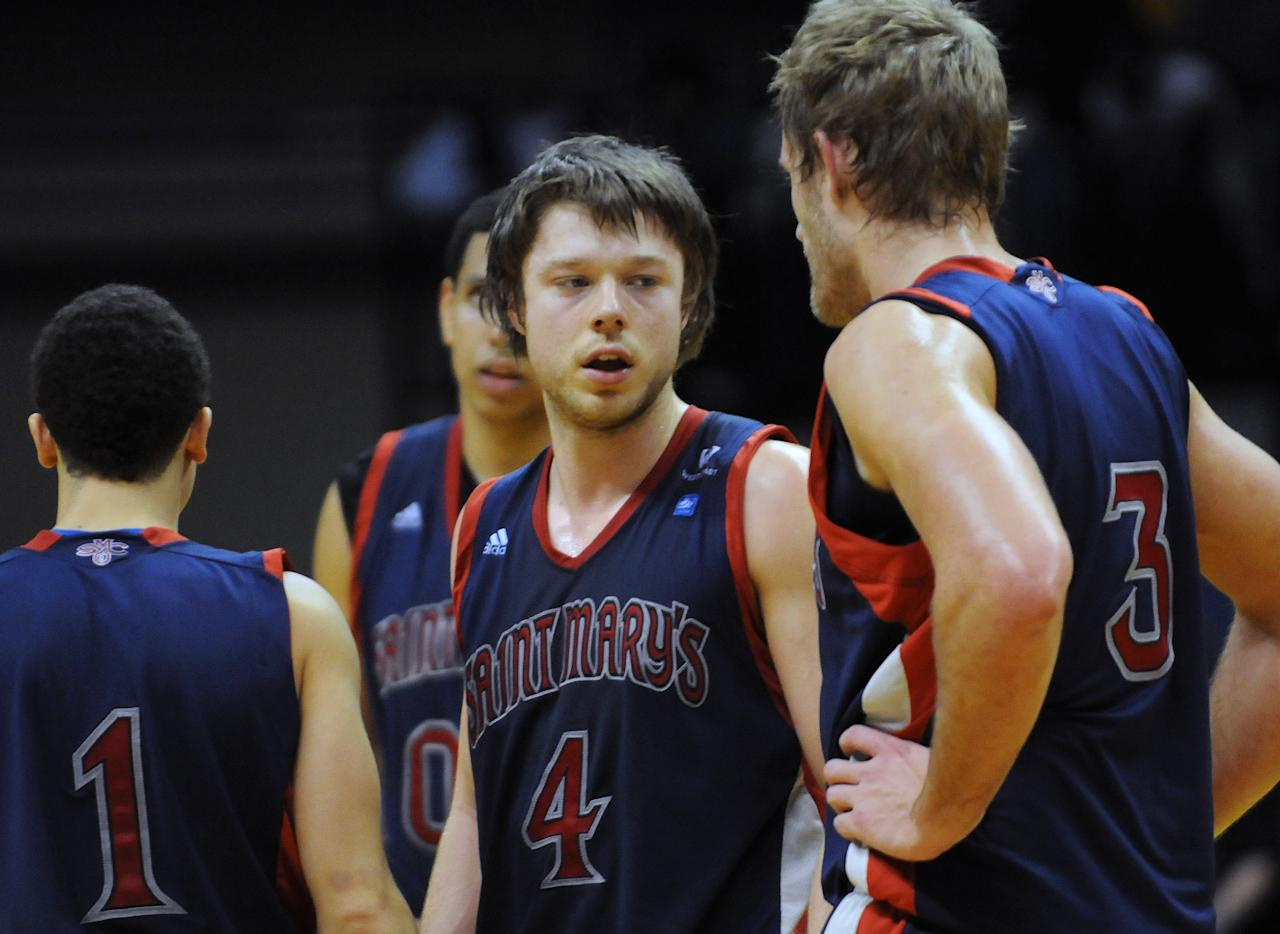 St. Mary's Matthew Dellavedova (4) talks with his teammates Jorden Page (1), Mitchell Young (3) and Brad Waldow during a timeout in the second half of an NCAA college basketball game against Murray State on Saturday, Feb. 18, 2012, in Murray, Ky. Murray State won 65-51. (AP Photo/Stephen Lance Dennee)
