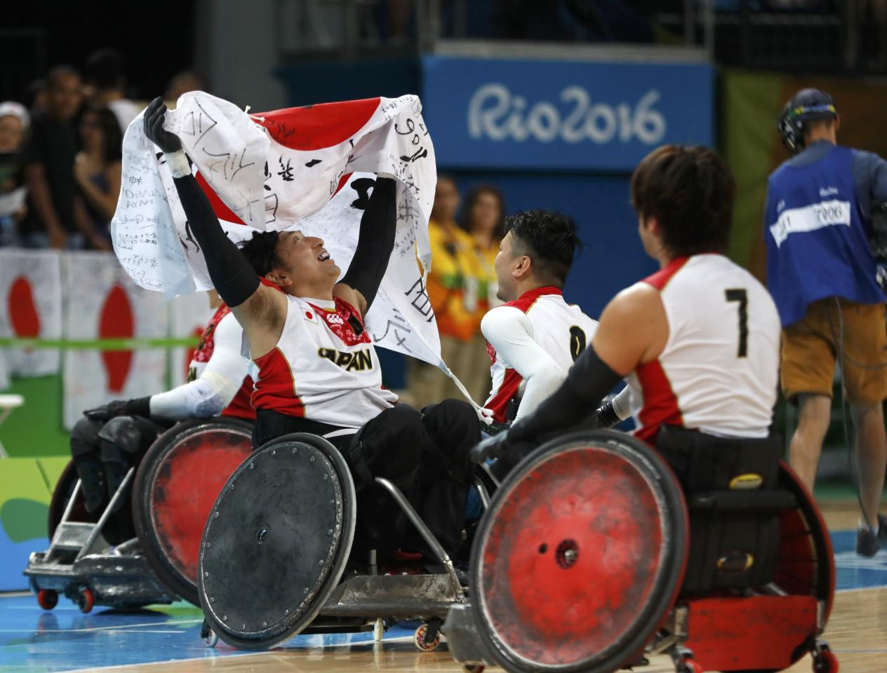 2016 Rio Paralympics - Wheelchair Rugby - Final - Mixed Team Bronze Medal Final - Japan v Canada - Carioca Arena 1 - Rio de Janeiro, Brazil - 18/09/2016. Kazuhiko Kanno (L) of Japan holds a national flag as hw with the teammates celebrates winning bronze medals. REUTERS/Carlos Garcia Rawlins  FOR EDITORIAL USE ONLY. NOT FOR SALE FOR MARKETING OR ADVERTISING CAMPAIGNS.