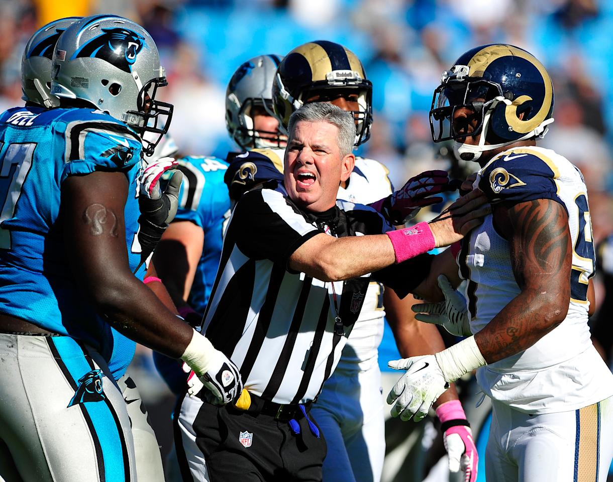 CHARLOTTE, NC - OCTOBER 20: Referee Bill Vinovich #52 separates Eugene Sims #97 of the St. Louis Rams and Byron Bell #77 of the Carolina Panthers as they scuffle during the fourth quarter at Bank of America Stadium on October 20, 2013 in Charlotte, North Carolina. The Panthers won 30-15. (Photo by Grant Halverson/Getty Images)