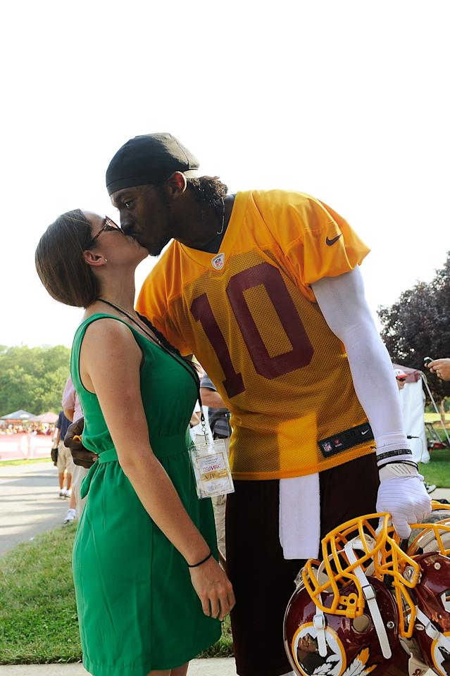 ASHBURN, VA - JULY 26:  Robert Griffin III #10 of the Washington Redskins kisses his fiancee Rebecca Liddicoat as he walks off the field during training camp at Redskins Park on July 26, 2012 in Ashburn, Virginia.  (Photo by Patrick McDermott/Getty Images)