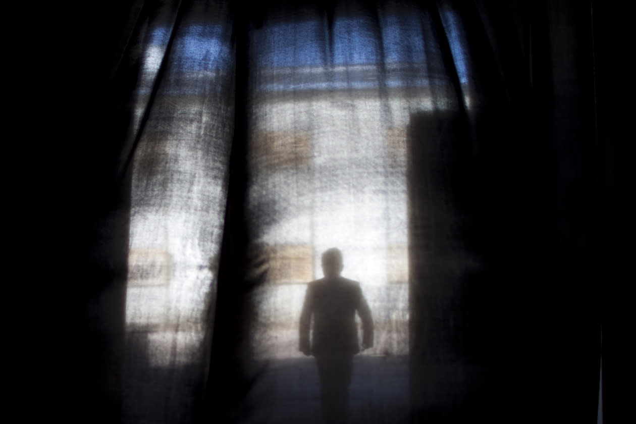 A man is seen through a door curtain as he leaves a hall showing designer furnitures.