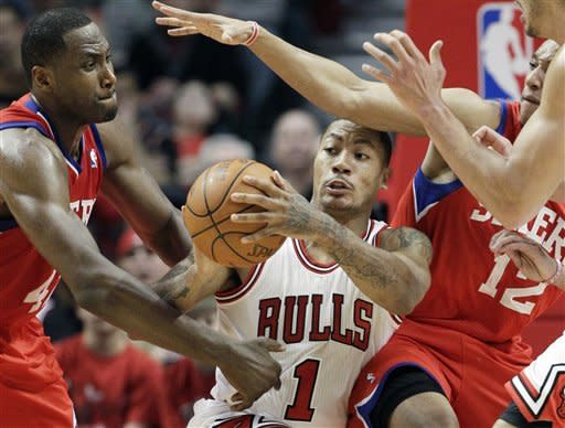 Chicago Bulls guard Derrick Rose (1) looks to a pass away from Philadelphia 76ers forward Elton Brand (42) and guard Evan Turner (12) during the second quarter of Game 1 in the first round of the NBA basketball playoffs in Chicago, Saturday, April 28, 2012. (AP Photo/Nam Y. Huh)