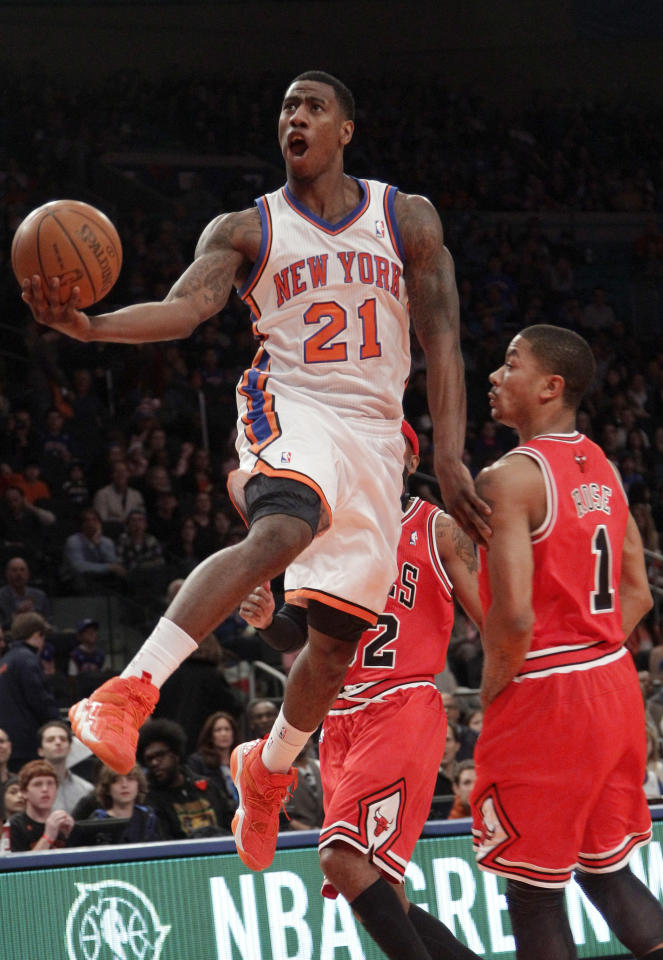 New York Knicks' Imam Shumpert goes up to the net past Chicago Bulls' Derrick Rose, right, during the first half of an NBA basketball game, Sunday, April 8, 2012, at Madison Square Garden in New York. (AP Photo/Mary Altaffer)