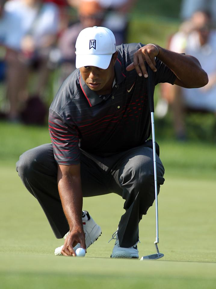 Tiger Woods places his ball on the 11th green during the first round of the Deutsche Bank Championship golf tournament at TPC Boston in Norton, Mass., Friday, Aug. 31, 2012. (AP Photo/Stew Milne)