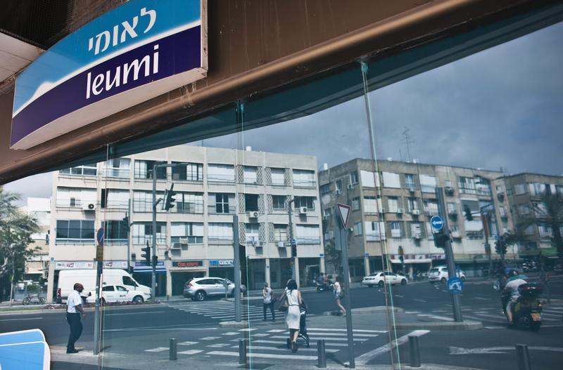 Pedestrians are reflected in windows of Bank Leumi branch in Tel Aviv