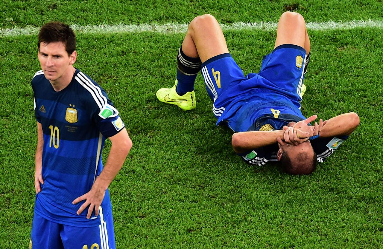 Argentina's Pablo Zabaleta lies on the pitch as Lionel Messi stands beside him after the World Cup final soccer match between Germany and Argentina at the Maracana Stadium in Rio de Janeiro, Brazil, Sunday, July 13, 2014. Mario Goetze volleyed in the winning goal in extra time to give Germany its fourth World Cup title with a 1-0 victory over Argentina on Sunday. (AP Photo/Francois Xavier Marit, Pool)