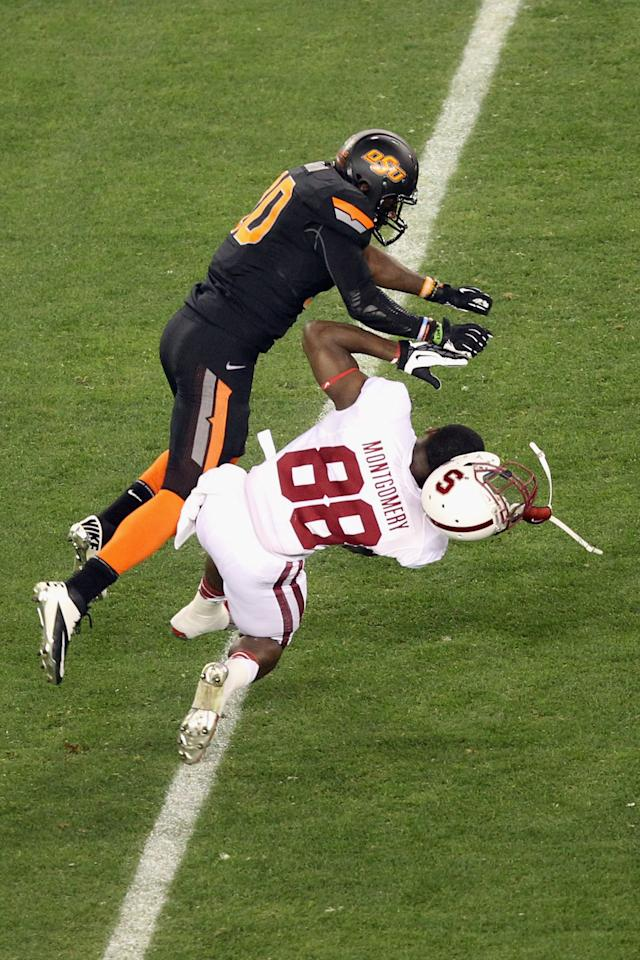 GLENDALE, AZ - JANUARY 02:  Ty Montgomery #88 of the Stanford Cardinal holds onto the ball for a reception but loses is helmet as he is tackled by Markelle Martin #10 of the Oklahoma State Cowboys during the Tostitos Fiesta Bowl on January 2, 2012 at University of Phoenix Stadium in Glendale, Arizona.  (Photo by Christian Petersen/Getty Images)