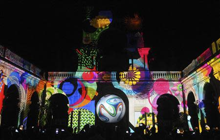 File photo of people taking pictures of the official match ball for the 2014 World Cup projected on a building at Lage Park in Rio de Janeiro