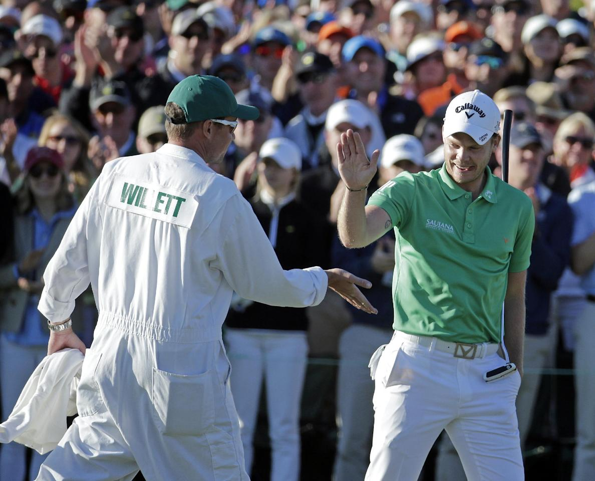 Danny Willett, of England, is congratulated by his caddie Jonathan Smart on the 18th hole after his final round of the Masters golf tournament Sunday, April 10, 2016, in Augusta, Ga. (AP Photo/Charlie Riedel)