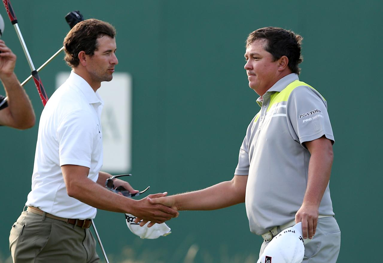 Adam Scott of Australia and Jason Dufner of the US, right, shake hands after finishing their round on the first day of the British Open Golf championship at the Royal Liverpool golf club, Hoylake, England, Thursday July 17, 2014. (AP Photo/Jon Super)