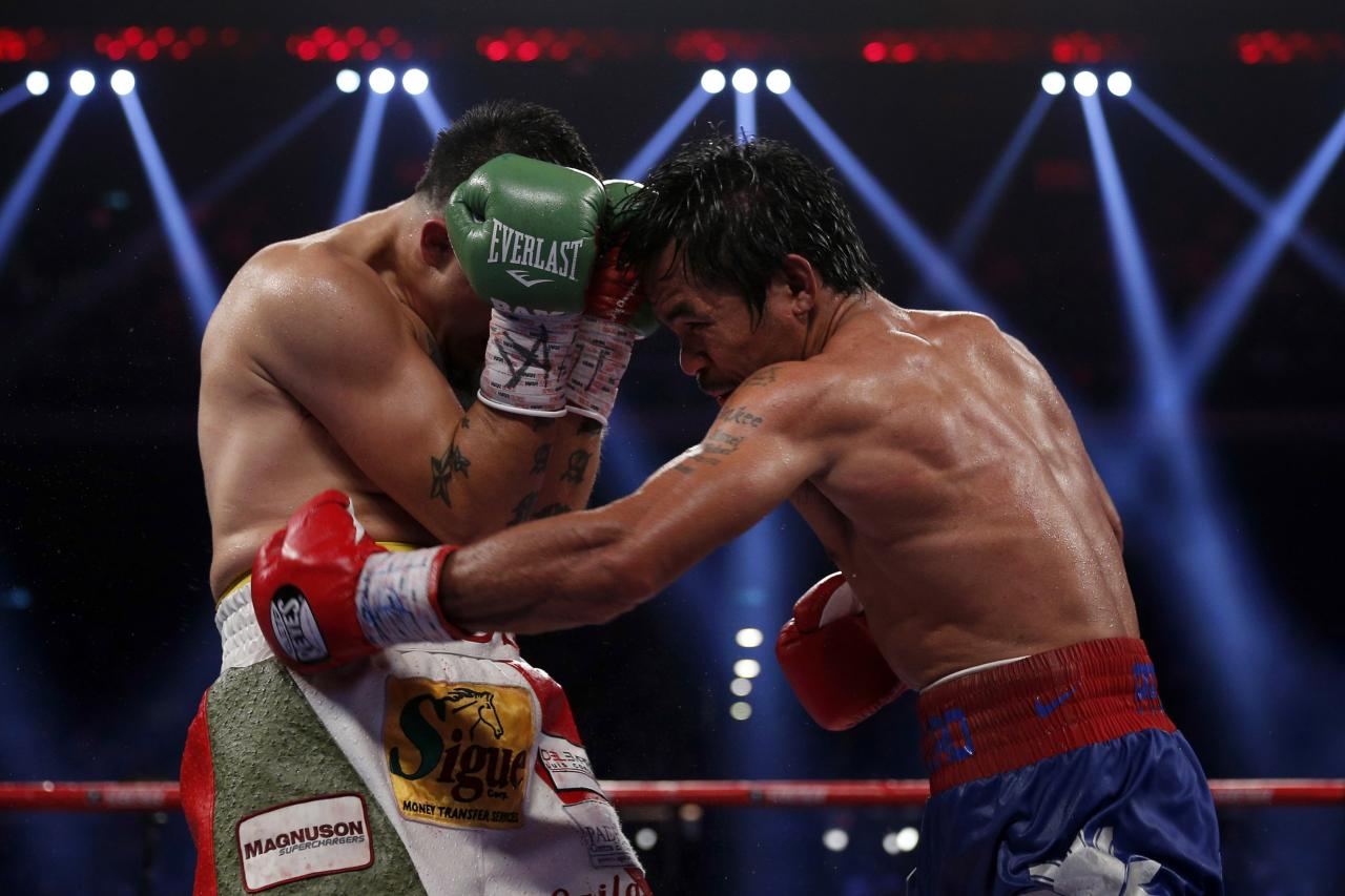 Manny Pacquiao of the Philippines punches on Brandon Rios (L) of the U.S. during their World Boxing Organisation (WBO) International 12-round welterweight boxing title fight at the Venetian Macao hotel in Macau November 24, 2013. Pacquiao registered a decisive, unanimous decision win against American Rios to clinch the vacant WBO International welterweight title on Sunday. REUTERS/Tyrone Siu (CHINA - Tags: SPORT BOXING)