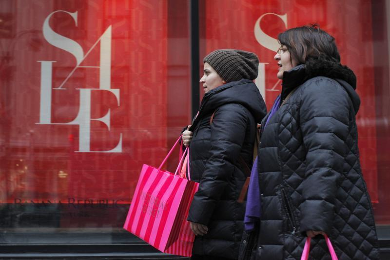 Shoppers walk past a shop while carrying shopping bags in New York