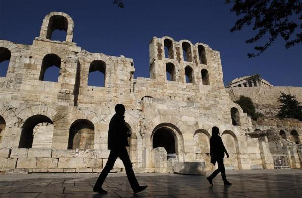 Tourists walk in front of the ancient Herodes Atticus theatre below the hill of the Acropolis in Athens November 28, 2011.