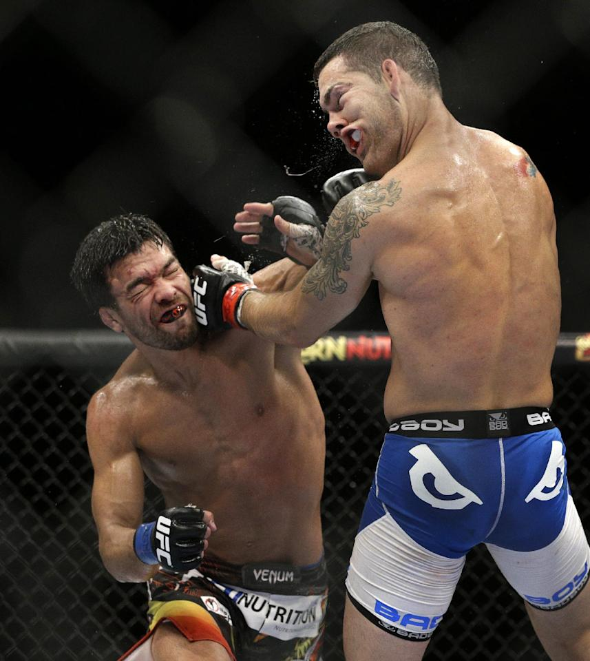 Lyoto Machida, left, hits Chris Weidman during their mixed martial arts middleweight title bout at UFC 175 Saturday, July 5, 2014, in Las Vegas. (AP Photo/John Locher)