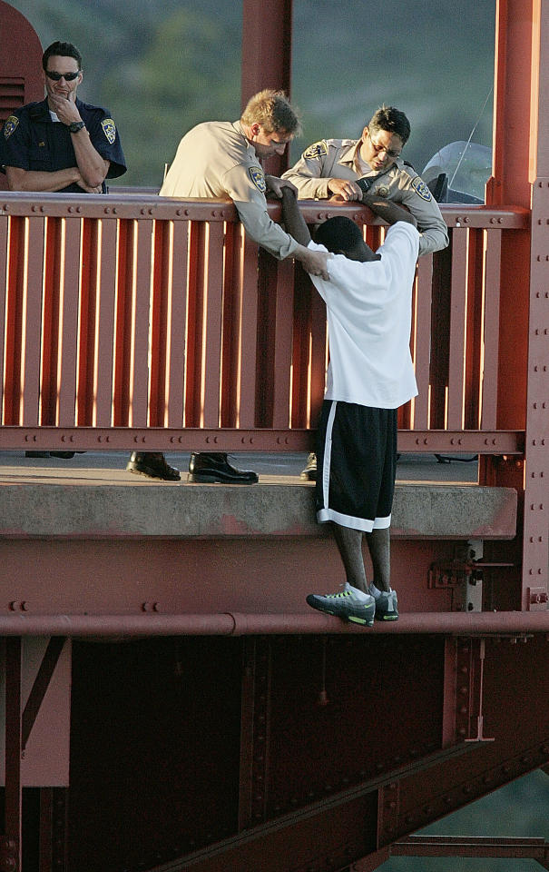 Sgt. Kevin Briggs convinces Kevin Berthia to cross back to the safe side of the rail on the Golden Gate Bridge on March 11, 2005. (John Storey/San Francisco Chronicle)