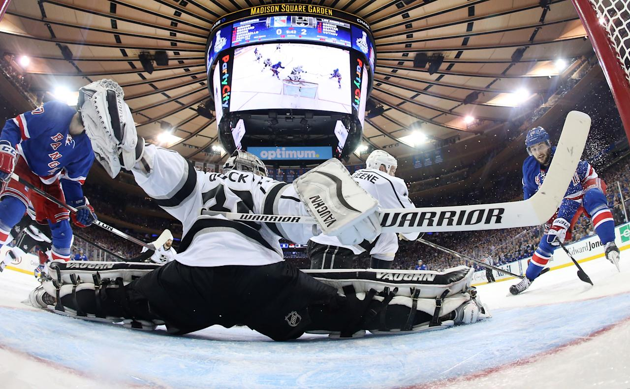 Los Angeles Kings goalie Jonathan Quick and teammate Matt Greene defend against New York Rangers Derick Brassard (16), right, and Benoit Pouliot in the second period during Game 3 of the NHL hockey Stanley Cup Final, Monday, June 9, 2014, in New York. (AP Photo/Bruce Bennett, Pool)