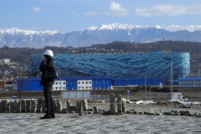 A visitor is on the phone in front of the Iceberg Skating Palace on February 17, 2012, during a press trip at the Russian Black Sea resort of Sochi, venue of the 2014 Winter Olympics games. The Games will be the biggest international event hosted by Russia since the collapse of the Soviet Union but it faces the challenge of building much of the facilities from scratch in Sochi city and the surrounding mountains. Sochi will host the 2014 Winter Olympics which will start on February 7, 2014. PHOTO / OLIVIER MORIN