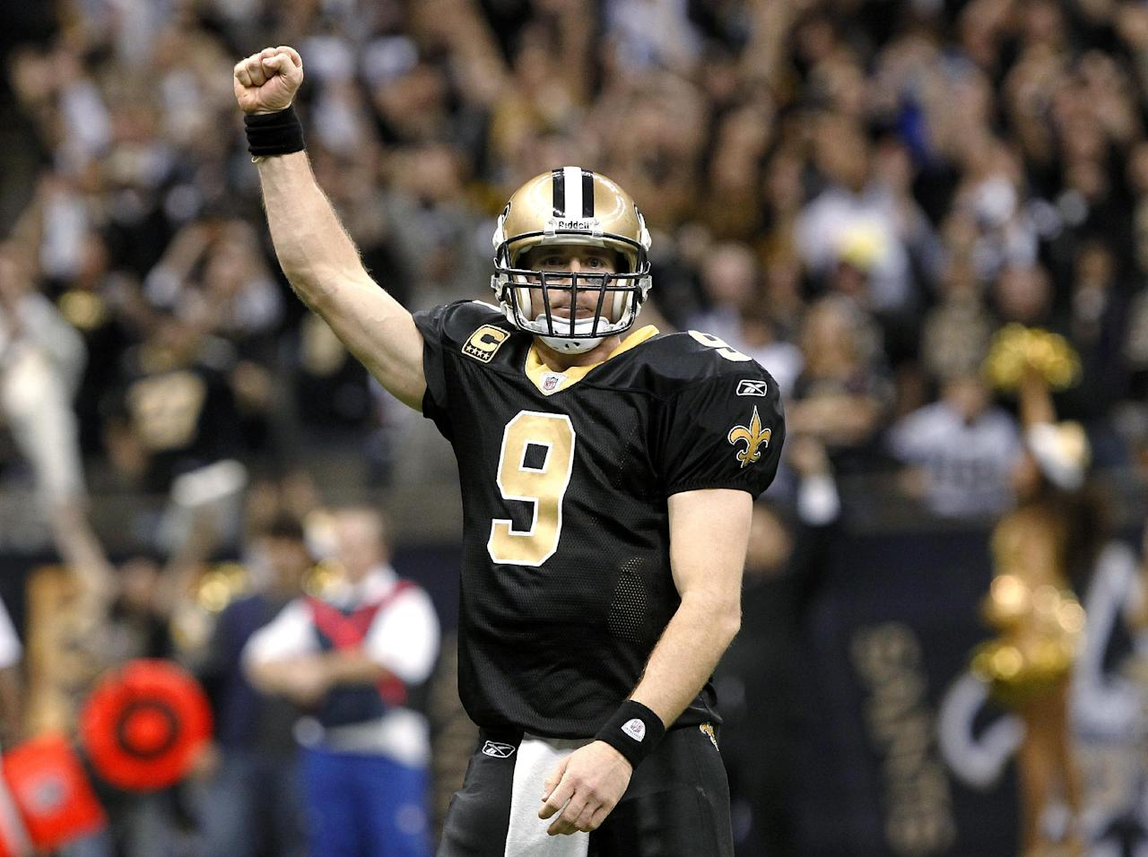 New Orleans Saints quarterback Drew Brees celebrates after throwing a touchdown pass and breaking the NFL single-season record for passing yardage, held by Dan Marino, in the fourth quarter of an NFL football game against the Atlanta Falcons in New Orleans, Monday, Dec. 26, 2011. (AP Photo/Rusty Costanza)