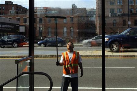 A worker washes the windows of a silver line bus station in Boston
