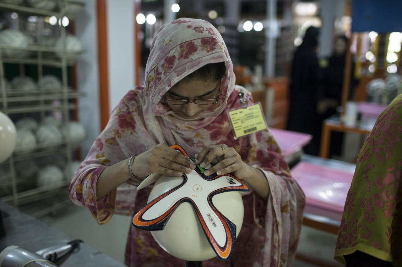 An employee adjusts outer panels of a soccer ball inside the soccer ball factory that produces official match balls for the 2014 World Cup in Brazil, in Sialkot, Punjab province May 16, 2014. It was when he felt the roar of the crowd at the 2006 World Cup in Germany that Pakistani factory owner Khawaja Akhtar first dreamt up a goal of his own: to manufacture the ball for the biggest soccer tournament on the planet. Last year he finally got his chance - but only 33 days to make it happen.Picture taken May 16. REUTERS/Sara Farid (PAKISTAN - Tags: SPORT SOCCER WORLD CUP BUSINESS EMPLOYMENT TPX IMAGES OF THE DAY)
