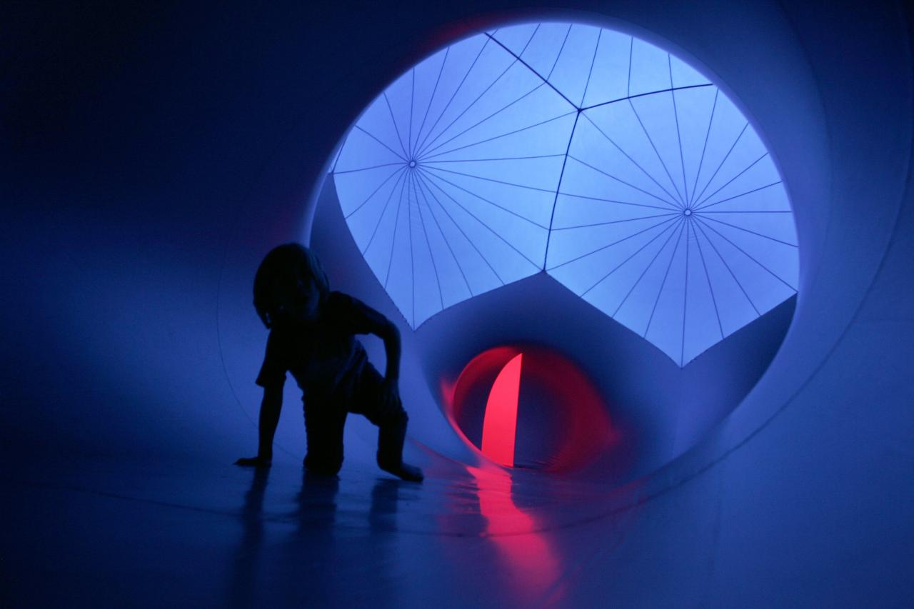 A child crawls on the floor of Exxopolis, an inflatable walk-in luminarium at Grand Park in Los Angeles, California, September 7, 2013. The inflatable walk-in luminarium, designed by Architects of Air, creates a maze of winding paths and domes featuring Islamic architecture, Archimedean solids, and Gothic cathedral designs. REUTERS/Jonathan Alcorn (UNITED STATES - Tags: SOCIETY)