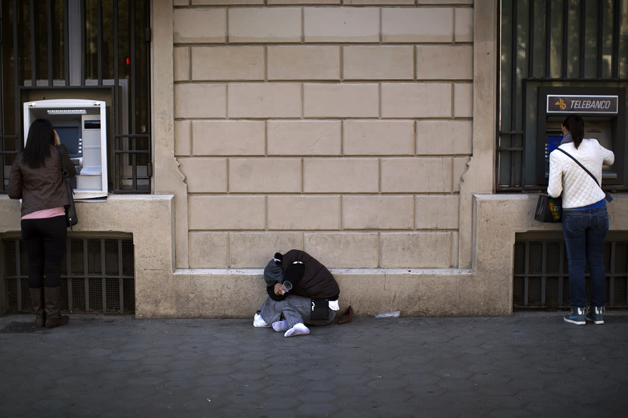 Two women withdraw money from cash dispensers as a beggar sleeps in the street in Barcelona.