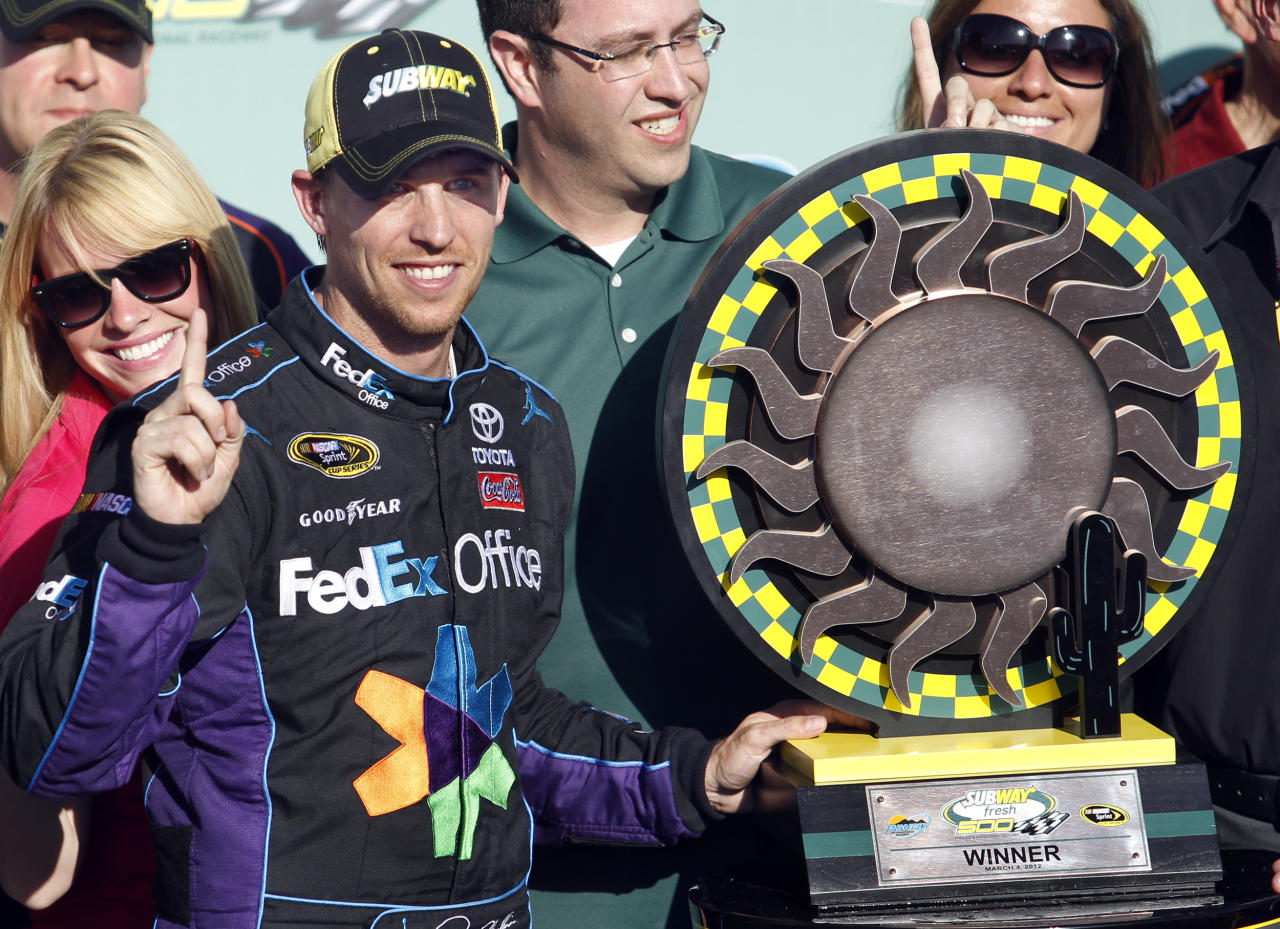 Denny Hamlin stands next to the trophy after winning the NASCAR Sprint Cup Series auto race at Phoenix International Raceway on Sunday, March 4, 2012, in Avondale, Ariz. (AP Photo/Paul Connors)