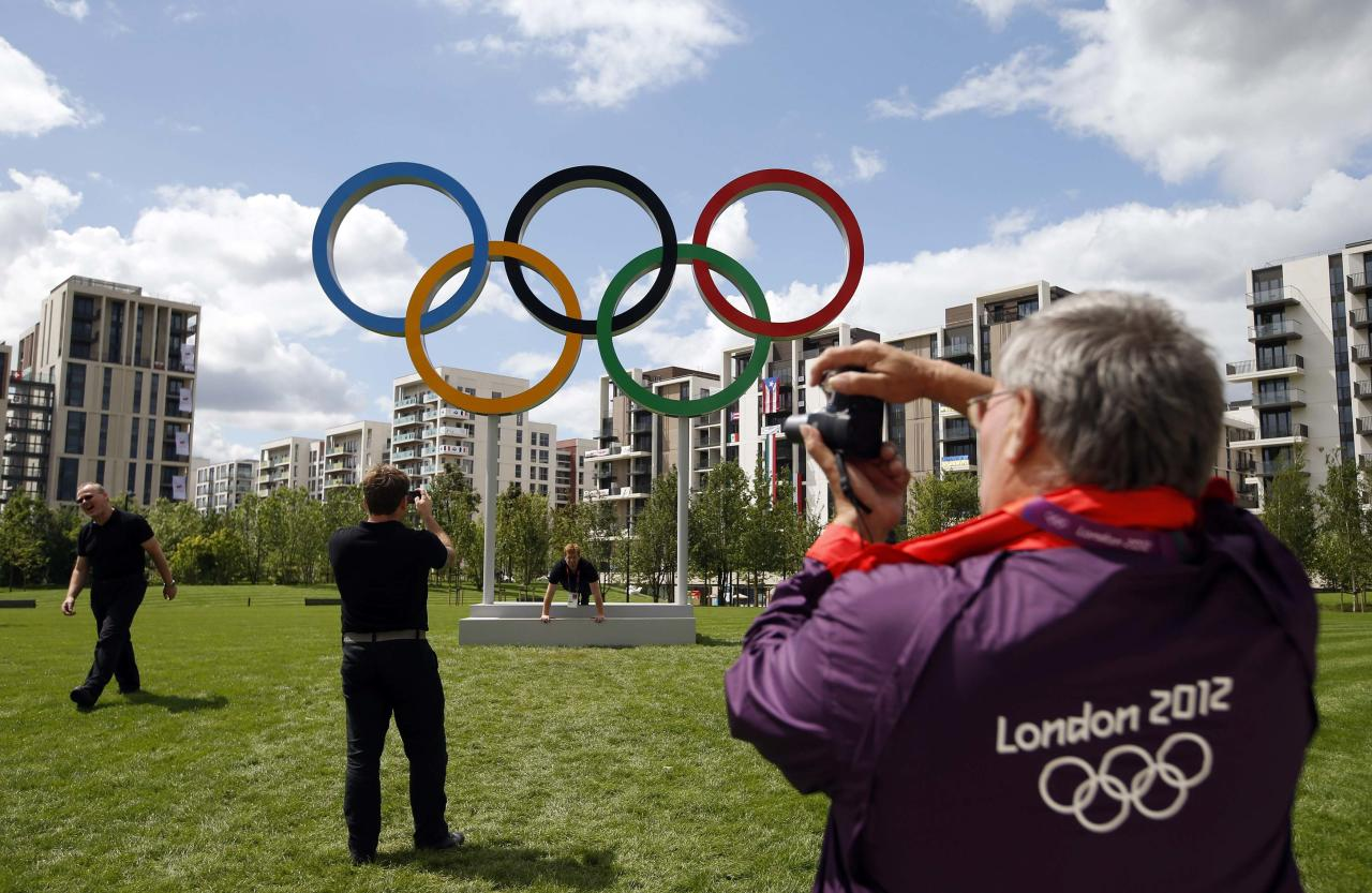 "A volunteer takes a photograph of the Olympic rings at the Athletes' Village at the Olympic Park in London in this July 19, 2012 file photo. Sleep deprived, rain-soaked and unpaid, London's army of  Olympic volunteers - officially known as ""games makers"" - are surprisingly upbeat, and have won admiration for their work shepherding thousands of fans around sports venues.   REUTERS/Jae C. Hong/Pool/Files (BRITAIN - Tags: SPORT OLYMPICS)"