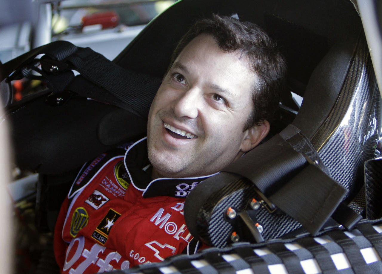 Driver Tony Stewart laughs with members of his crew just before going out on the track during NASCAR auto racing testing at the Daytona International Speedway, Thursday, Jan. 12, 2012, in Daytona Beach, Fla. (AP Photo/John Raoux)