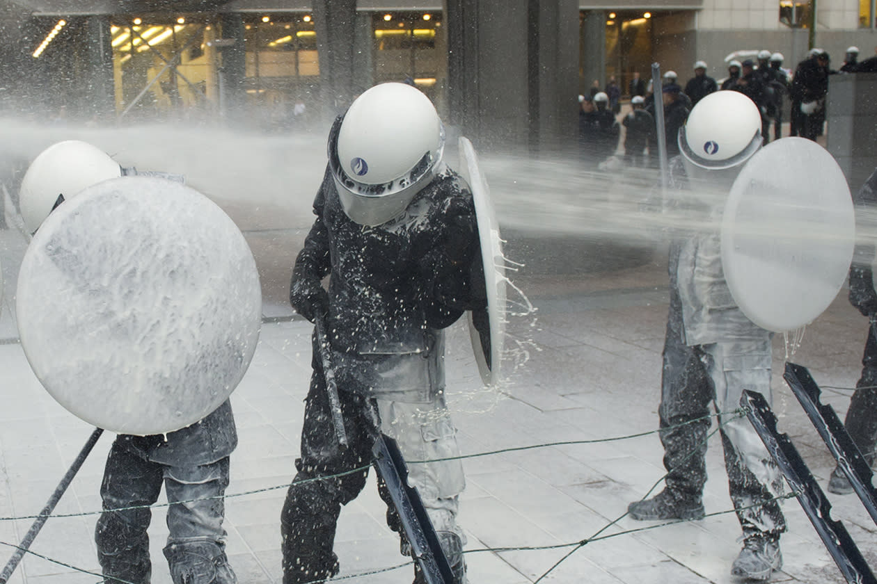 Police officers are sprayed with milk by the European milk farmers during a demonstration in front of the European Parliament building in Brussels.