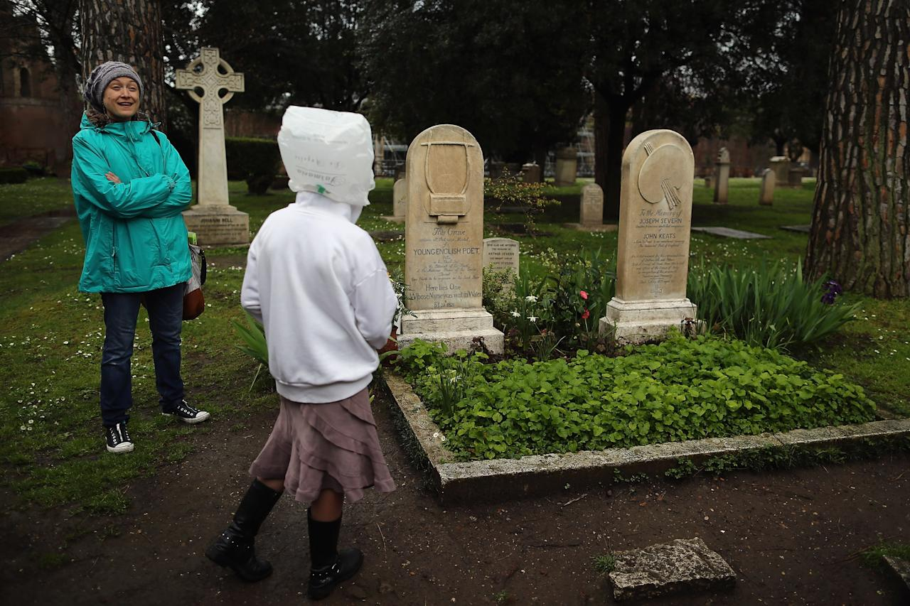 ROME, ITALY - MARCH 26:  Visitors look at the gravestones of poet John Keats, (1795-1821), (L) and painter and friend Joseph Severn, (1803-79) (R) lie in Rome's 'Non Catholic Cemetery' on March 26, 2013 in Rome, Italy. John Keats, one of England's most famous poets died early in 1820 of tuberculosis aged 25, after travelling to Italy in search of a better climate to help cure him of the disease. Rome's Non-Catholic Cemetery contains one of the highest densities of famous and important graves anywhere in the world. It is the final resting-place of the poets Percy Shelley and John Keats, as well as many other painters, sculptors and authors who died in Rome. The cemetery which began it's use in 1730 continues today, containing graves of Orthodox Christians, Jews, Muslims and other non-Christians, and is one of the oldest burial grounds in Europe.  (Photo by Dan Kitwood/Getty Images)