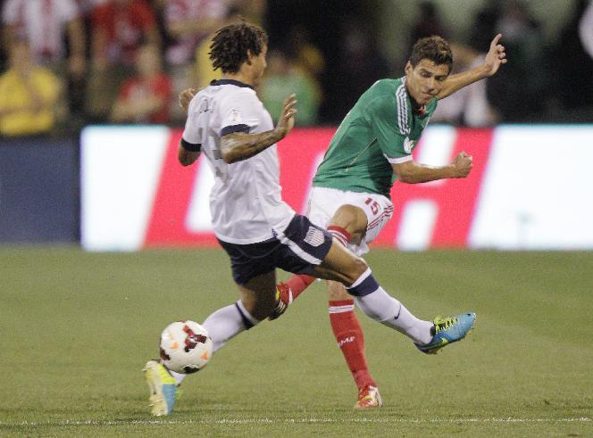 Mexico's Hector Moreno, right, shoots the ball past the United States' Jermaine Jones during the first half of a World Cup qualifying soccer match Tuesday, Sept. 10, 2013, in Columbus, Ohio. (AP Photo/Jay LaPrete)