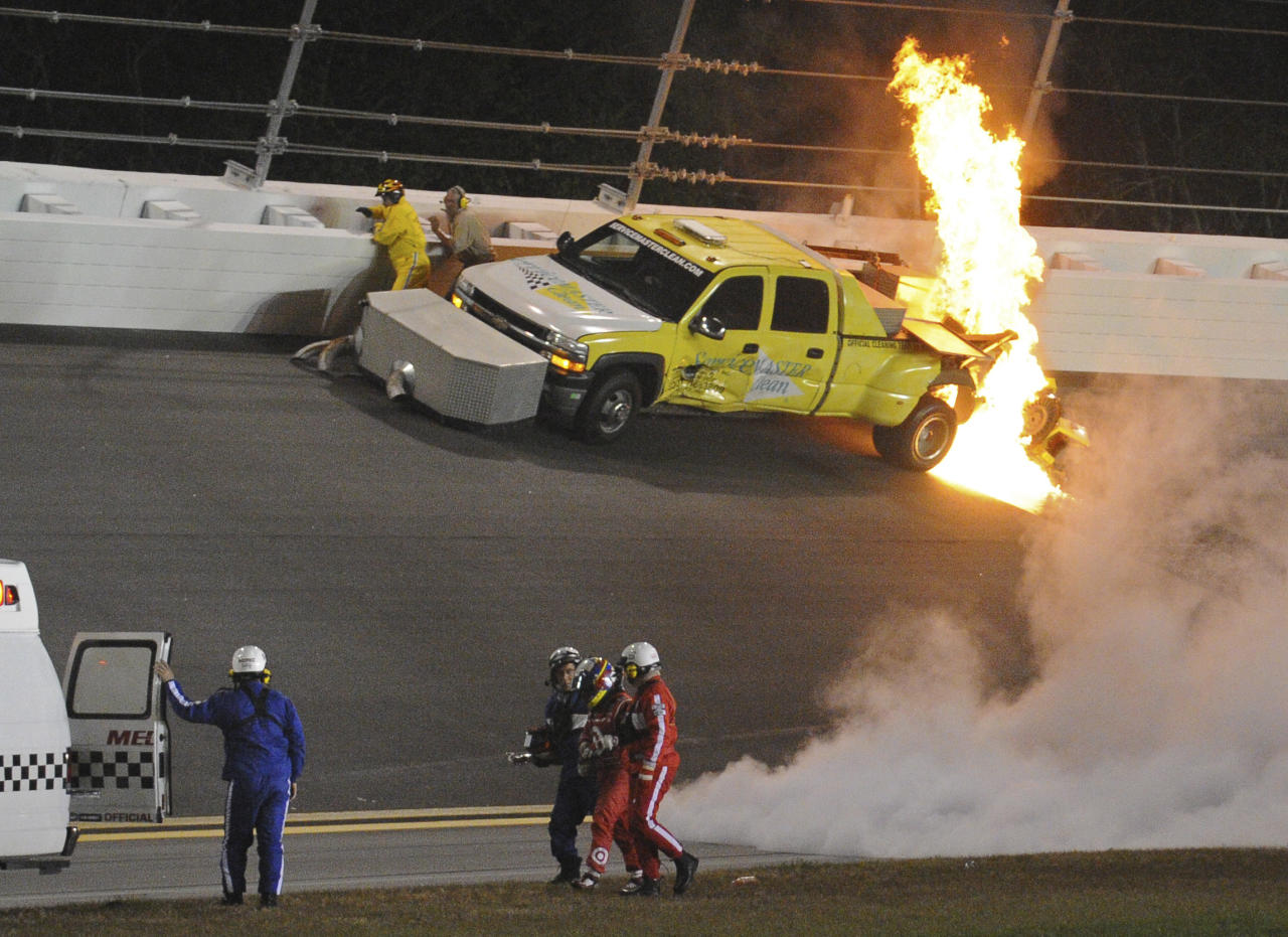 Emergency personnel walk with Juan Pablo Montoya, of Colombia, to an ambulance after his car struck a jet dryer during a caution period in the NASCAR Daytona 500 auto race at Daytona International Speedway in Daytona Beach, Fla., Monday, Feb. 27, 2012. The fuel in the dryer began burning. (AP Photo/Rob Sweeten)